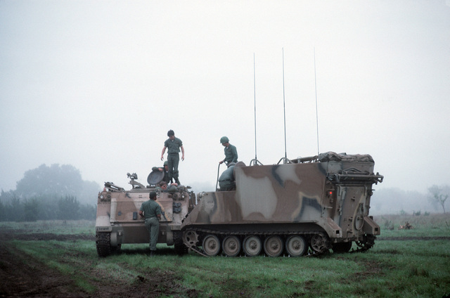 US Army soldiers man an M557A1 armored command vehicle, right, and an M113 armored personnel carrier during a field training exercise