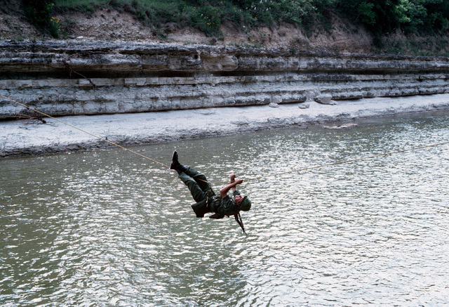 A rope suspended across a river serves as a crossing for a soldier during a training exercise