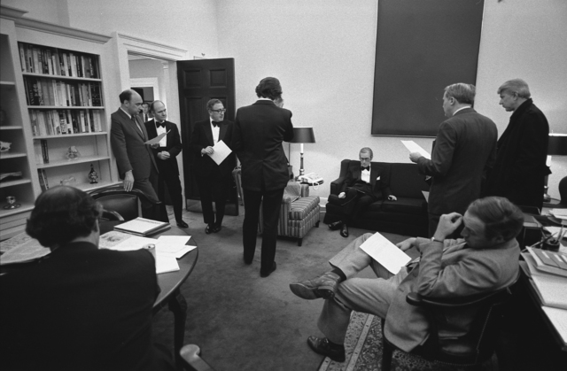 Photograph of Secretary of State Henry A. Kissinger, Chief of Staff Donald Rumsfeld, Richard Cheney, Counsellor John O. Marsh, Press Secretary Ron Nessen, Deputy National Security Adviser Brent Scowcroft, and NSC Staff Monitoring Messages from the Evacuation of Saigon, Vietnam, Prior to a Stag Dinner Honoring King Hussein of Jordan