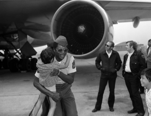GUNNERY Sergeant (GYSGT) Larry Eaton of the Air Freight Section helps a Vietnamese child as refugees arrive at the air station. After being processed at the air station passenger terminal, the refugees will depart for Marine Corps Base, Camp Pendleton