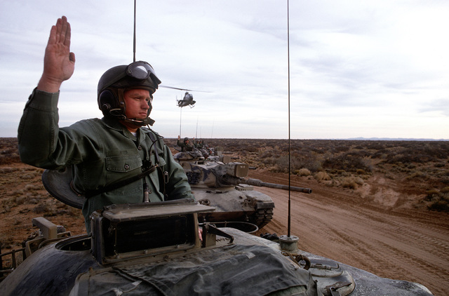U.S. Army soldiers give hand signals from the turrets of their M-60 main battle tanks during a field training exercise. An AH-1 Cobra helicopter is hovering overhead
