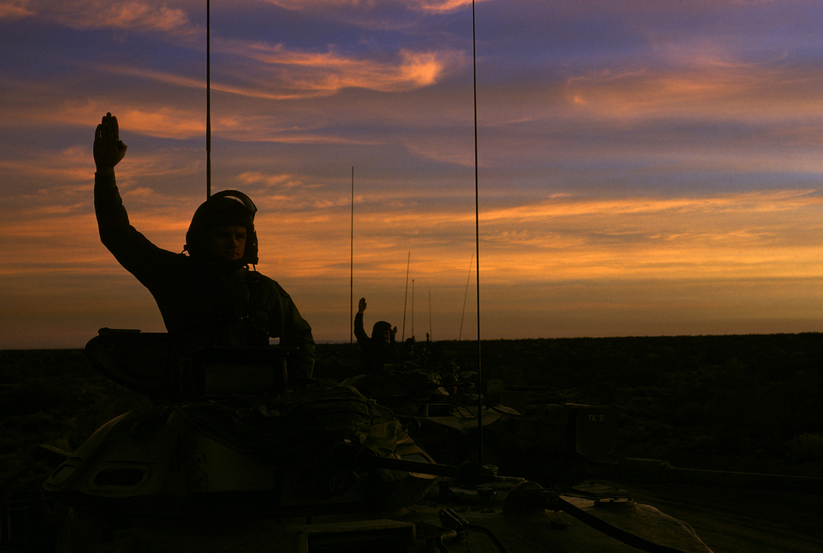 US Army soldiers give hand signals from the turrets of their M60 main battle tanks at dusk during a field training exercise