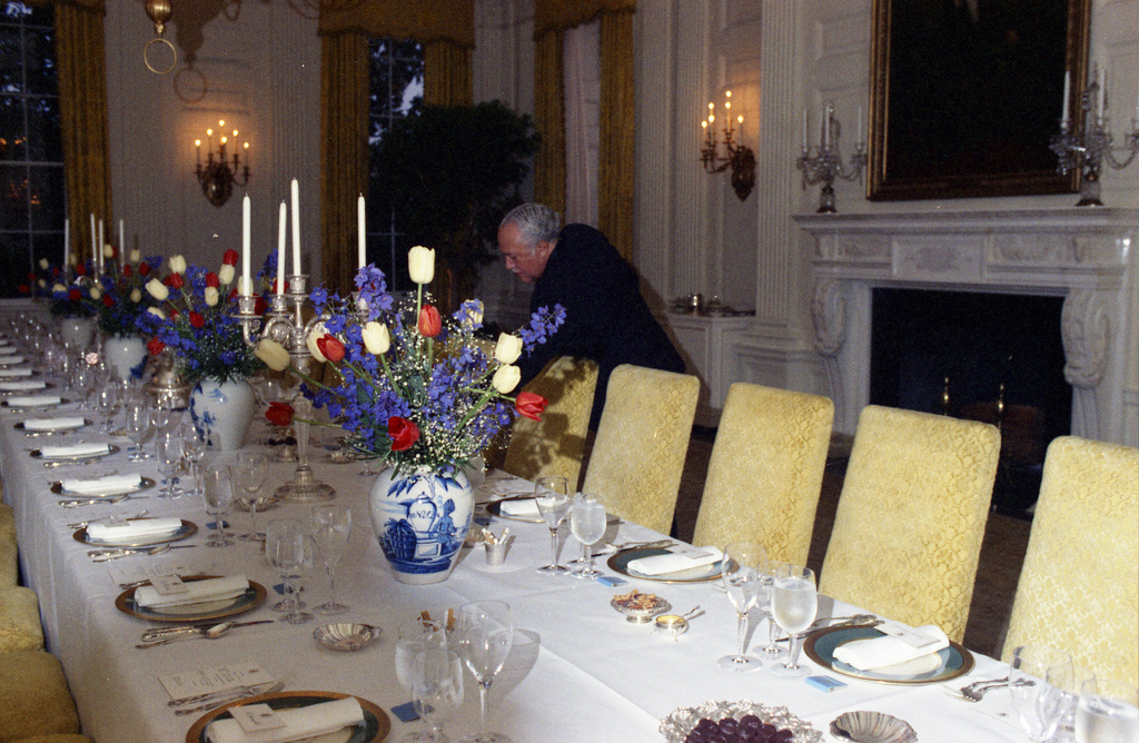Photograph of White House Maitre d' John Ficklin Checking Table Settings in the State Dining Room Prior to a Stag Dinner Honoring the Prime Minister of the Netherlands