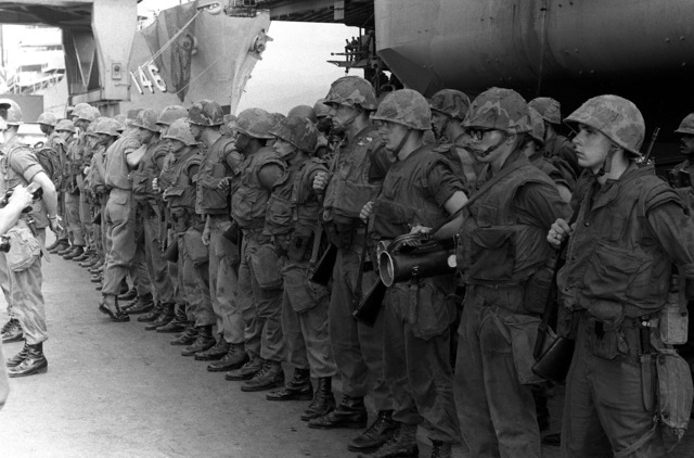 U.S. Marines from Co. G and Co. E, 2nd Bn., 9th Marines, prepare to depart the aircraft carrier USS CORAL SEA (CV-43) following the rescue operation of the merchant vessel SS MAYAGUEZ and the Kon Tang Island Operation