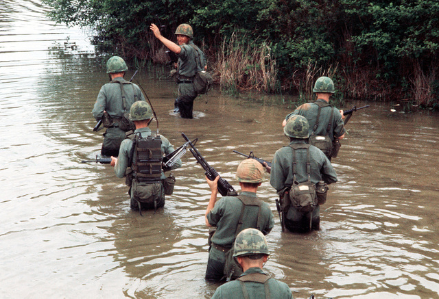 Army troops wade through a marshy area during a training