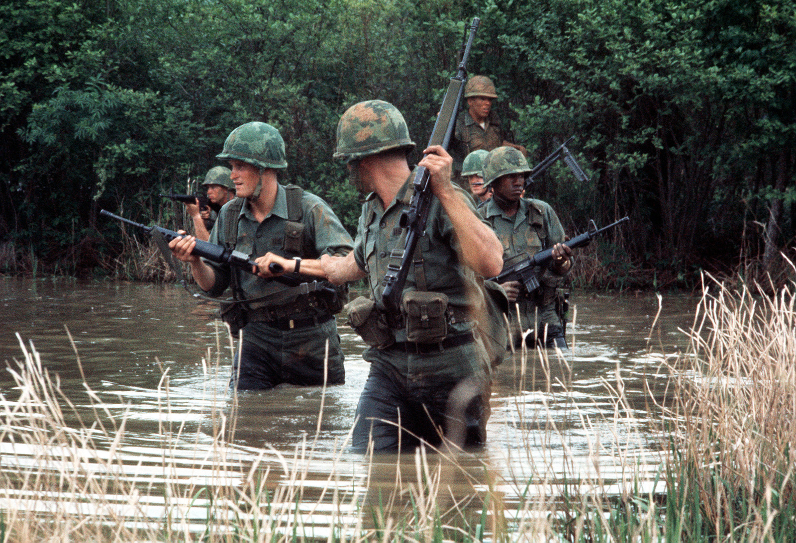 Army troops wade through a marshy area during a training exercise