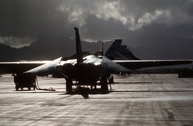 A right rear view of an F-111 aircraft half silhouetted by sunlight amid dark clouds. Twenty-six F-111 aircraft of the 347th Tactical Fighter Wing are being redeployed from Korat Air Base, Thailand, to the United States due to a reduction in forces