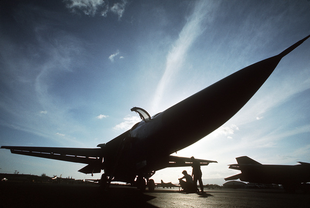 A view of an F-111 aircraft silhouetted against the sunset during a rest stop at the base. Twenty-six F-111 aircraft of the 347th Tactical Fighter Wing are being redeployed from Korat Air Base, Thailand, to the United States because of a reduction in forces