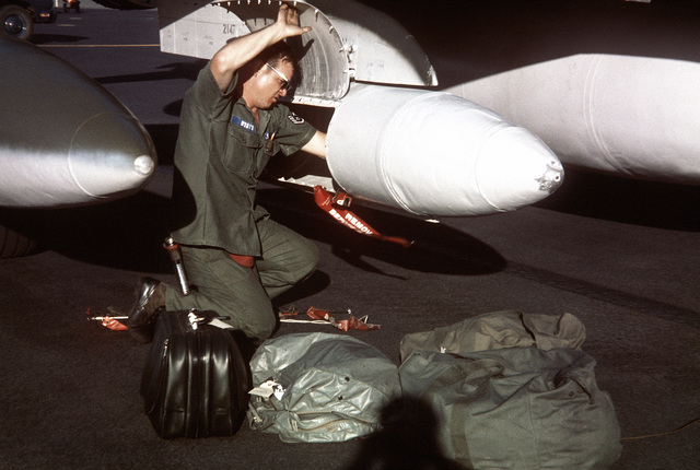 A maintenance crewman unloads fly-away kits from the luggage pod of an F-4 Phantom II aircraft from the 34th Tactical Fighter Squadron during a rest stop at the base. The redeployment of F-4 aircraft from Korat Air Base, Thailand, to the United States because of a reduction in forces is known as Coronet Slice and began on July 22, 1975