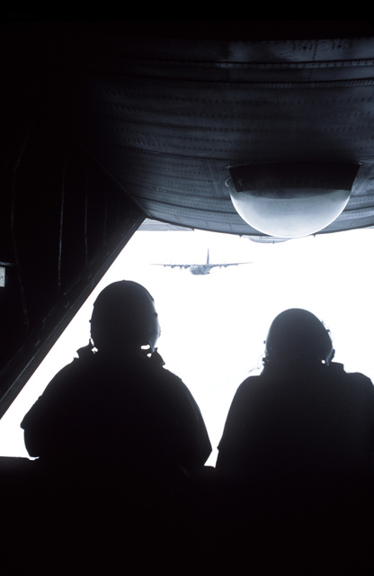 Two crew members are positioned at the open ramp of an AC-130H Hercules aircraft during a training flight. Another AC-130H is in the background. The airmen are assigned to the 16th Special Operations Squadron, 388th Tactical Fighter Wing