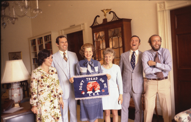 """First Lady Betty Ford Displaying Her """"Bloomer"""" Flag with Agent Dick Hartwig, White House Marine Corps Aide Rick Sardo, White House Photographer David Hume Kennerly, and East Wing Staff Members Kaye Pullen and Carolyn Porembka"""