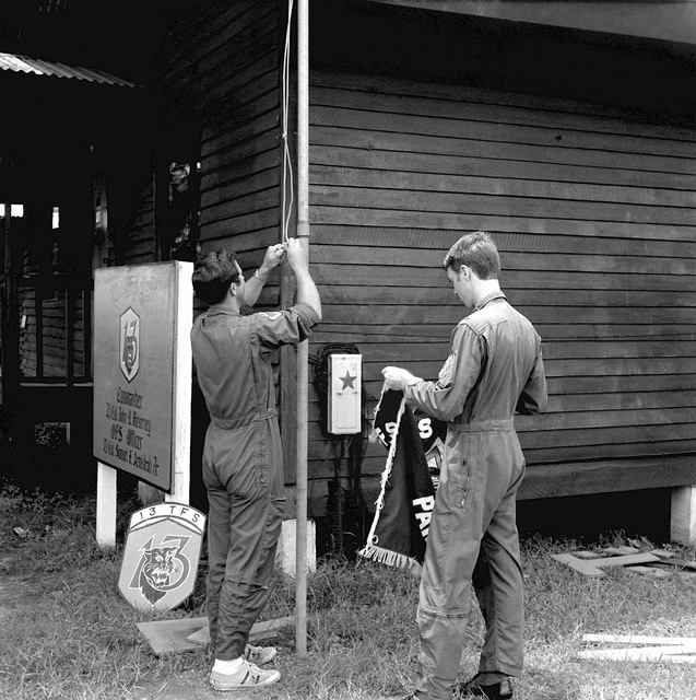 """1LT Jerry Mikinis and 1LT Thomas W. Steves, left to right, take down the squadron flag for the last time. The 13th Tactical Fighter Squadron, """"Panther Pack,"""" was deactivated on June 30, 1975"""