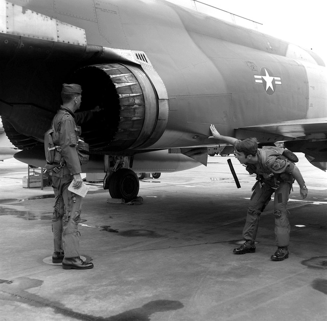 """2LT Herbert Winkeller and LTC John W. Meservey, left to right, check over their F-4D Phantom II aircraft before leading the first flight of F-4's from the base. The 13th Tactical Fighter Squadron, """"Panther Pack,"""" was deactivated on June 30, 1975"""