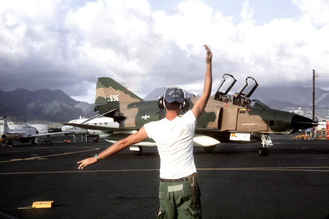 A ground crewman directs an RF-4C Phantom II aircraft into a parking spot while on a rest stop during Operation Coronet Hook, the redeployment of 22 F-4 and RF-4C Phantom II aircraft from Udorn Royal Thai Air Force Base, Thailand, and Kadena Air Base, Okinawa, to the United States because of a reduction in forces