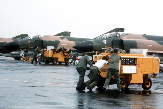 A maintenance crew moves M-32 A-60 generators into position to service F-4 Phantom II aircraft during a rest stop. The equipment is being used during redeployment of F-4's of the 34th Tactical Fighter Squadron from Korat Royal Thai Air Force Base, Thailand, to the United States because of a reduction in forces