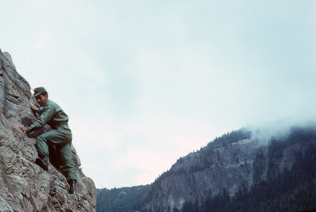 A US Army soldier scales a mountain during a field training exercise