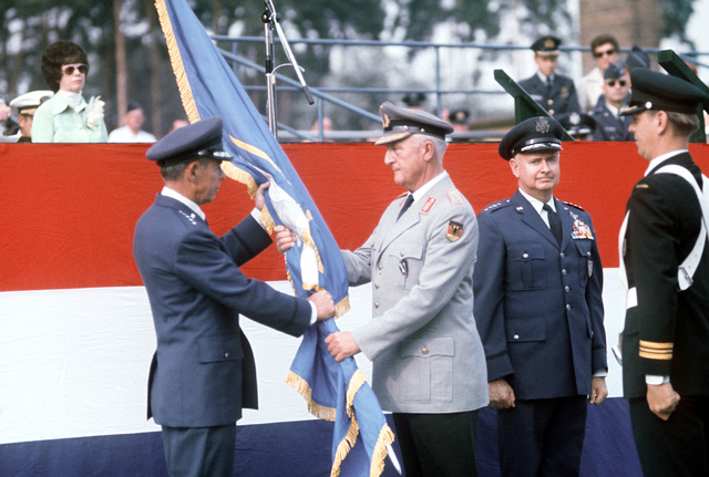 GEN Richard H. Ellis, incoming commander, receives the NATO flag from GEN Ferber, German Air Force, as GEN John W. Vogt, outgoing commander, stands by during the Allied Air Force Central Europe (AAFCE) change of command
