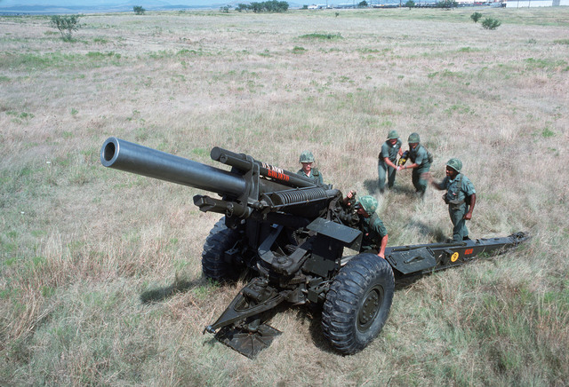 A US Army artillery crew loads an M114 155 mm howitzer during a training exercise