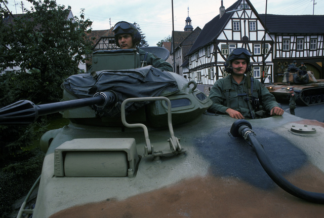 US Army tank crewmen look out from the turret of an M60 main battle tank during a field training exercise