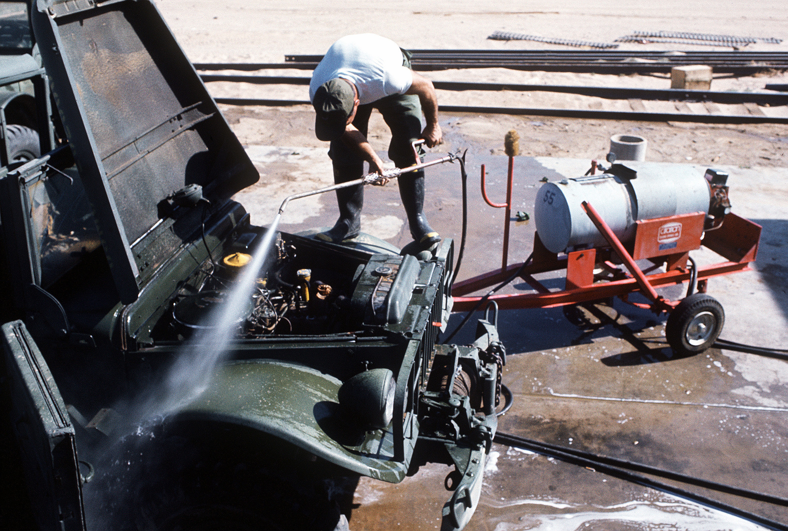 An airman cleans one of the military-design vehicles that the Air National Guard (ANG) is acquiring from the Marine Corps. The acquisition and rehabilitation project will save the Air Force about seven million dollars