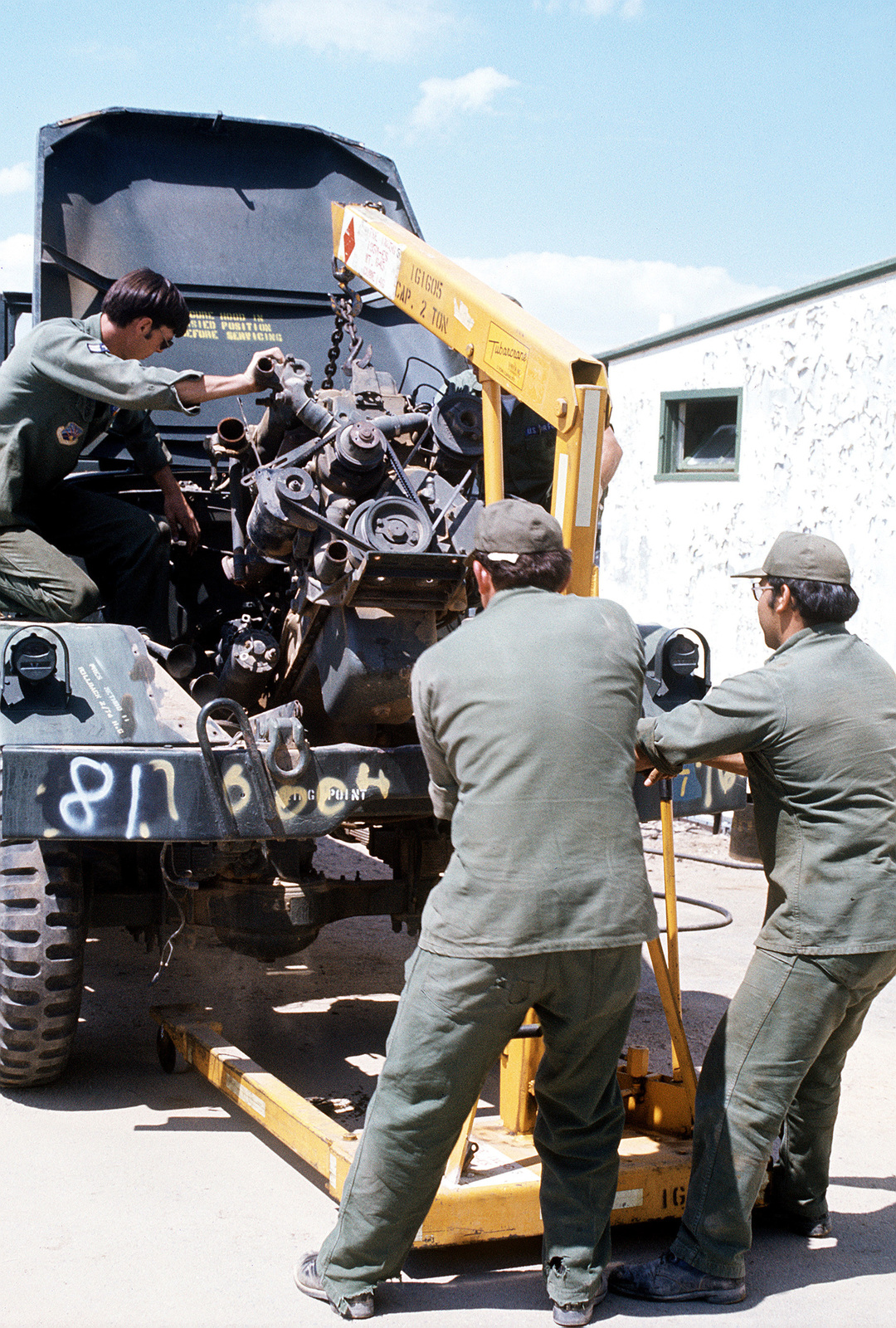 Three Air National Guardsmen remove the engine of a vehicle during rehabilitation operations. The vehicle is one of over 600 acquired from the Marine Corps in an acquisition and rehabilitation project that will save the Air Force about seven million dollars