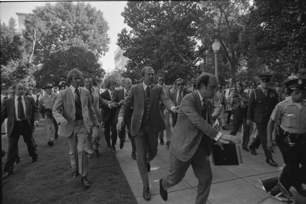 """Photograph of Secret Service Agents Rushing President Gerald Ford Towards the California State Capitol following the Assassination Attempt on the President by Lynette """"Squeaky"""" Fromme, in Sacramento, California"""