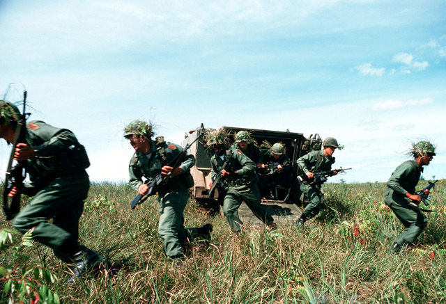 Army troops rush out of an armored personnel carrier during a training exercise