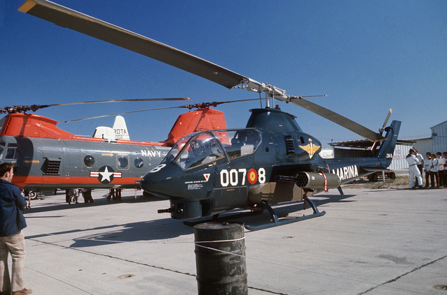 A left front view of a Spanish navy AH-1S Cobra helicopter and a US Navy HH-46A Sea Knight helicopter parked on the flight line