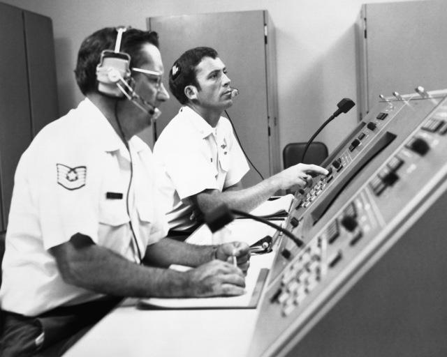 Control Operator TSGT Ernest Bergmann and Instructor Navigator MAJ Robert Woodrow, left to right, operate the controls of T-45 navigator simulators during training
