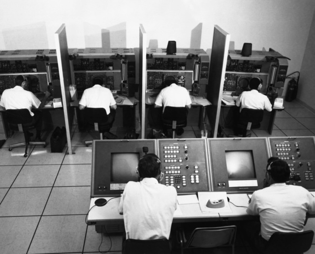 United States Air Force officers train on T-45 navigator simulators as Instructor Navigator MAJ Robert Woodrow and Control Operator TSGT Ernest Gergmann, left to right, operate the controls of the complex