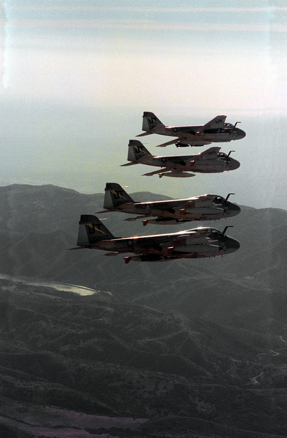 An air-to-air right side view of four A-6A Intruder aircraft in echelon formation. The aircraft are assigned to Marine All-Weather Medium Attack Squadron 242 (VMA(AW)-242)