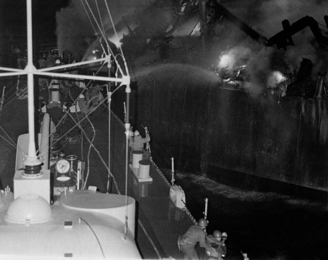 Firefighters aboard the guided missile destroyer USS CLAUDE V. RICKETTS (DDG 5) direct spray from their hoses onto a fire aboard the guided missile cruiser USS BELKNAP (CG 26).  The BELKNAP was heavily damaged and caught fire when it collided with the aircraft carrier USS JOHN F. KENNEDY (CV 67) during night operations
