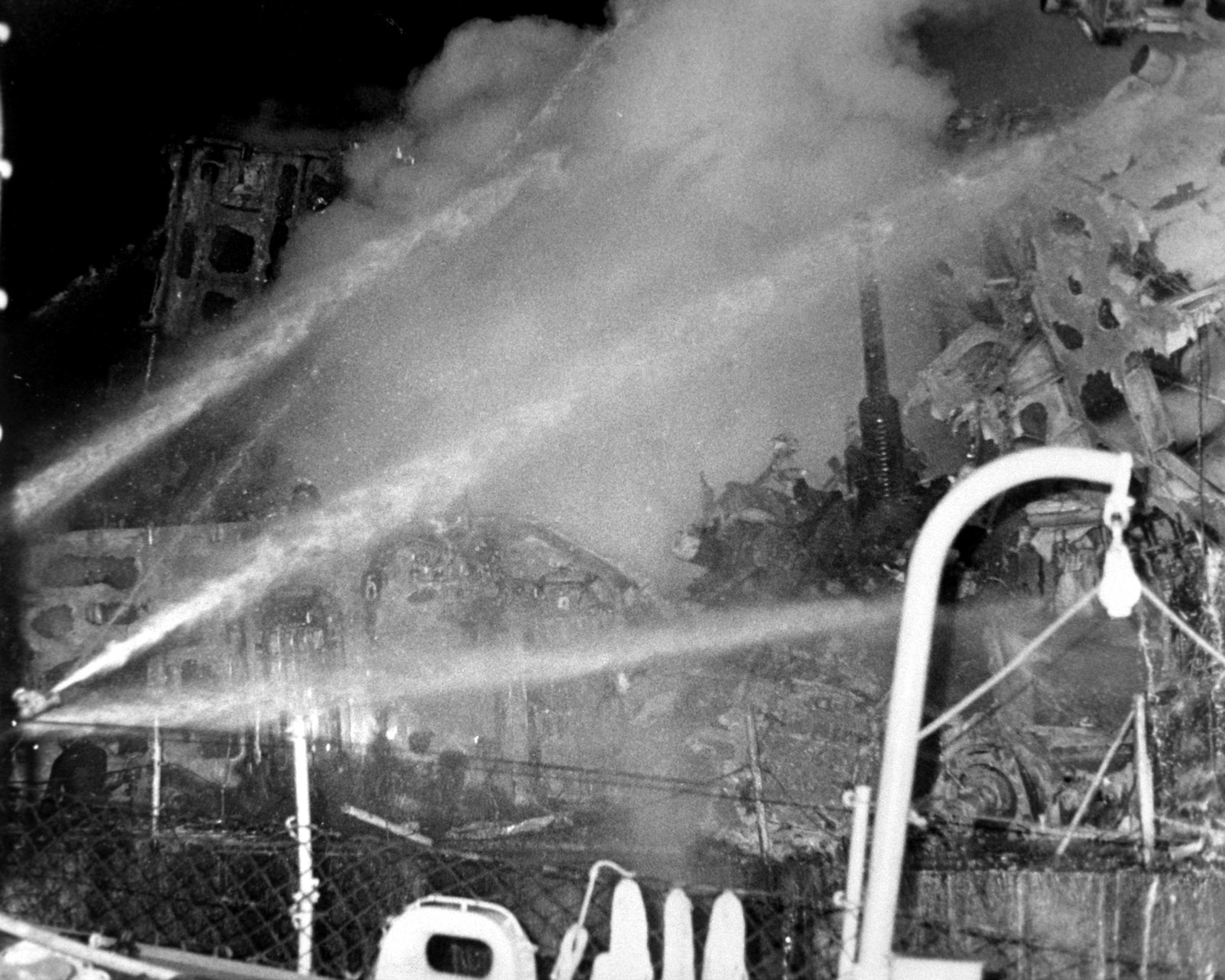 Firefighters aboard the guided missile destroyer USS CLAUDE V. RICKETTS (DDG-5) direct spray from their hoses onto a fire aboard the guided missile cruiser USS BELKNAP (CG-26). The BELKNAP was heavily damaged and caught fire when it collided with the aircraft carrier USS JOHN F. KENNEDY (CV-67) during night operations