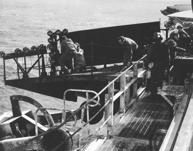 Ionian Sea.  Crew members prepare to remove the Fresnel lens optical landing system from the aircraft carrier USS JOHN F. KENNEDY (CV 67).  The system was damaged when the carrier collided with the guided missile cruiser USS BELKNAP (CG 26) during night operations on November 22, 1975