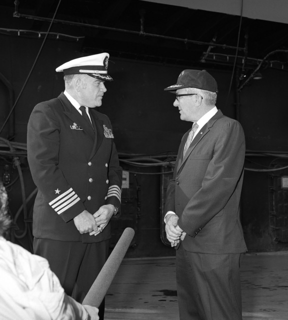 Captain (CAPT) Charles Miller, master of the merchant vessel SS MAYAGUEZ, right, visits with CAPT Joseph F. Frick, commanding officer of the aircraft carrier USS CORAL SEA (CV 43), to thank him and his crew for their participation in the rescue of the MAYAGUEZ and its crew from Cambodia