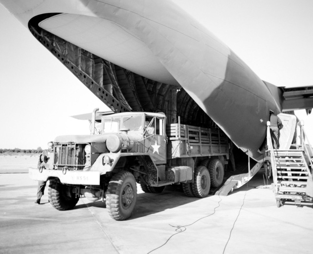 A cargo truck is offloaded from a YC-15 aircraft during a heavy loading test