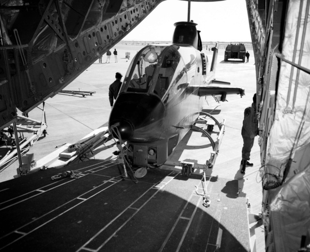 An AH-1G Cobra helicopter is offloaded from a YC-15 aircraft during a heavy loading test