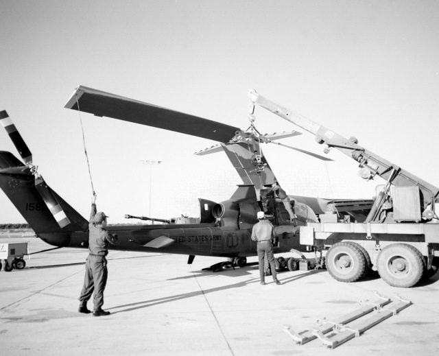 The rotor blades are removed prior to loading an AH-1G Cobra helicopter aboard a YC-15 aircraft during a heavy loading test