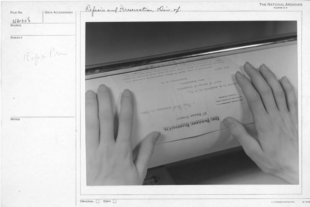 Photograph of a Document Being Flattened in the Repair and Preservation Division