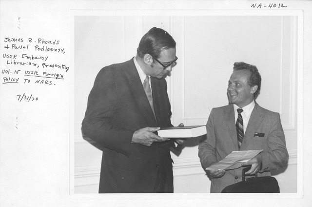 Photograph of James B. Rhoads and Pavel Podlesnyy, USSR (The Union of Soviet Socialist Republics) Embassy Librarian Presenting Vol. 15 USSR Foreign Policy to NARS