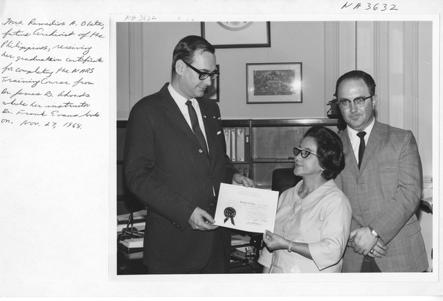 Photograph of Mrs. Remedios A. Oleta Receiving a NARS Graduation Certificate from Dr. James B. Rhoads, Archivist of the United States with Instructor Dr. Frank Evans