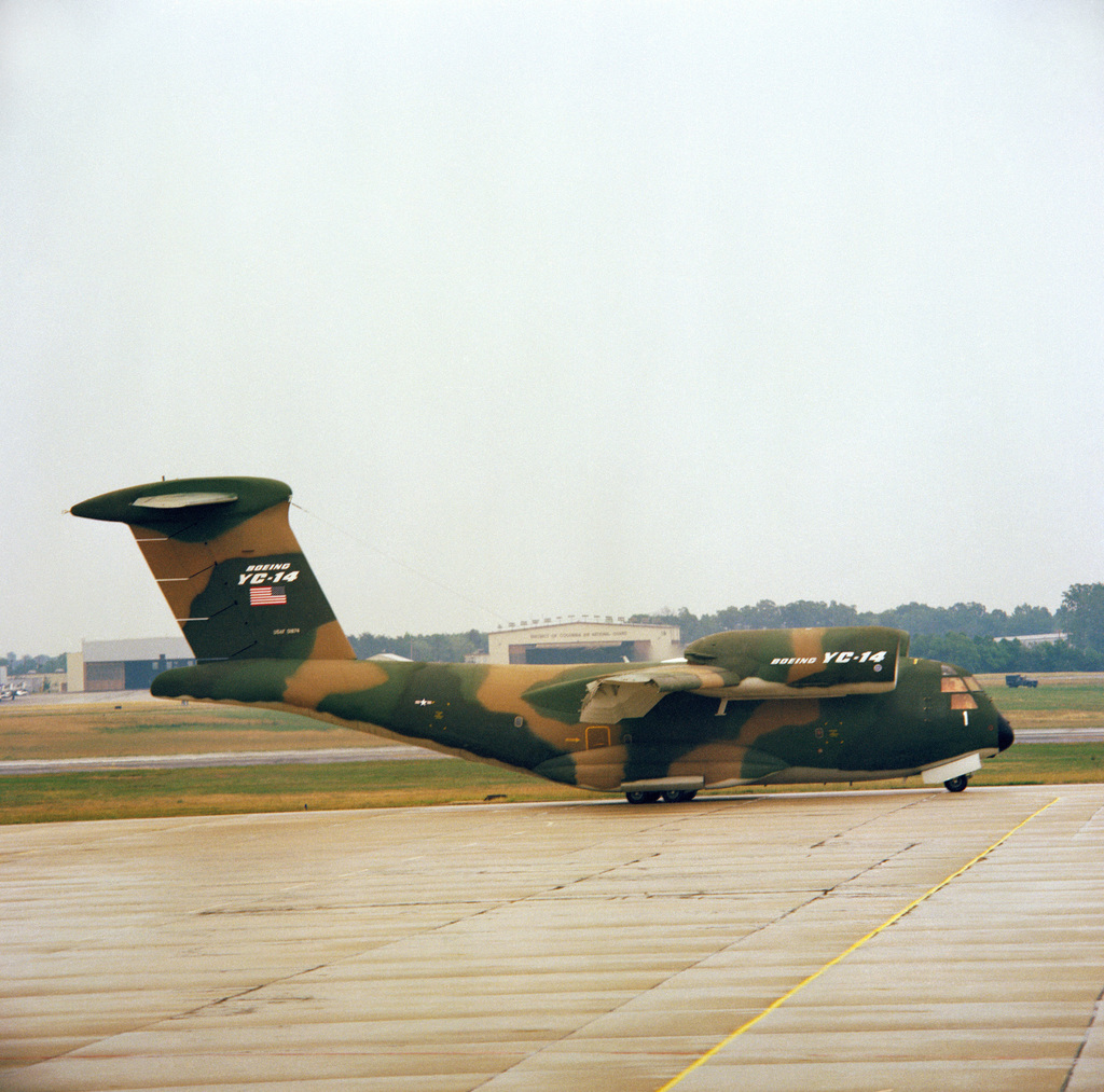 A right side view of a YC-14A aircraft parked on the flight line