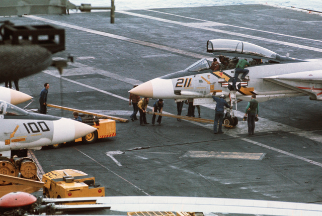 Crewmen service an F-14 Tomcat aircraft on the flight deck of the aircraft carrier USS AMERICA (CV 66)