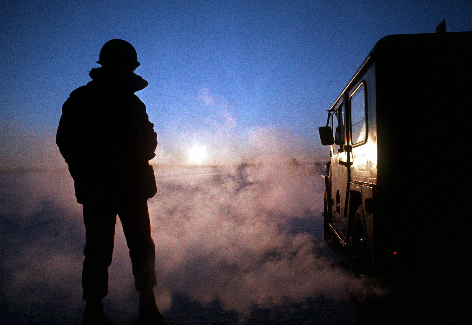 Silhouetted view of a combat control team members, with the sent in the background during Exercise Jack Frost '76