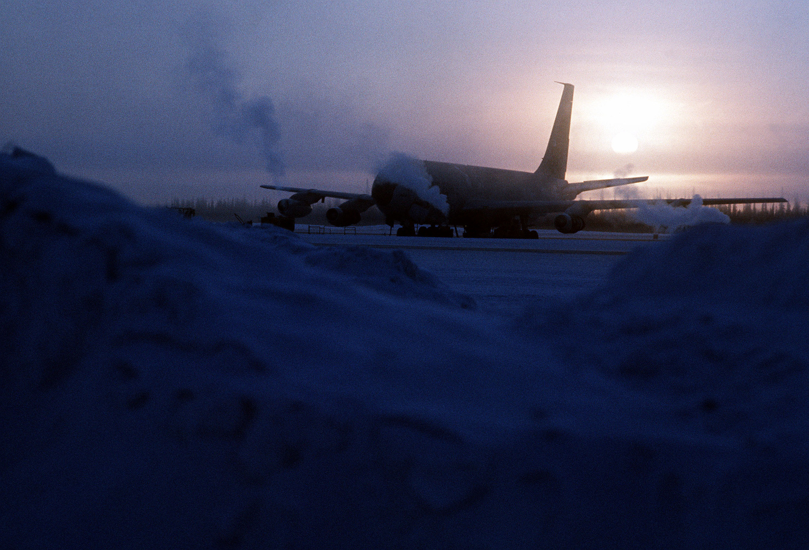 Silhouette view of a KC-135 Stratotanker aircraft as the sun sets behind it, during Exercise Jack Frost '76