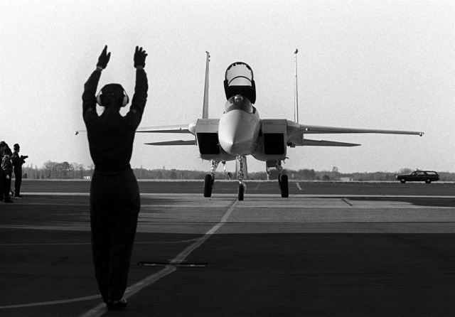A flight line crewman directs the first F-15A Eagle aircraft assigned to the base to a parking spot on the flight line