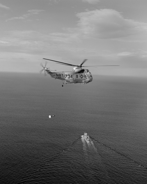 An air-to-air right rear view of an SH-3A Sea King helicopter from Helicopter Anti-submarine Squadron 6 (HS-6) with AN/ASQ-81 magnetic anomaly detection (MAD) gear suspended below it. Visible below is a frigate underway