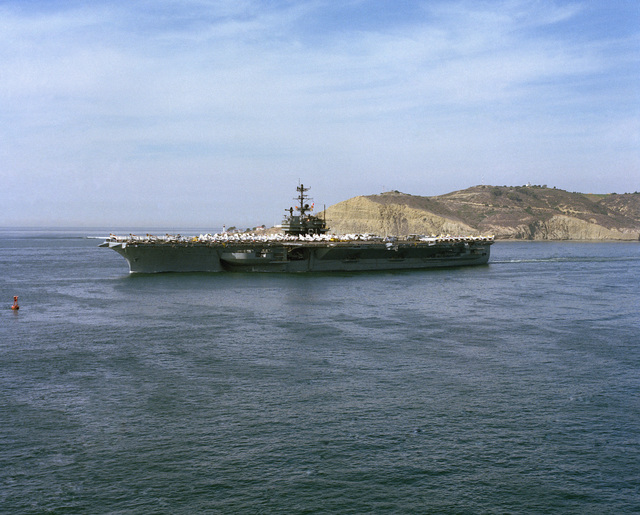 An elevated port bow view of the aircraft carrier USS RANGER (CV 61) departing San Diego for deployment in the western Pacific. The ship is passing Pt. Loma. (SUBSTANDARD)