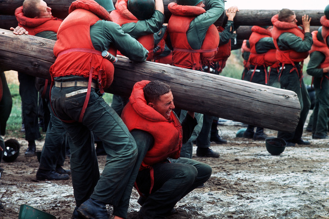 """A U.S. Navy Basic Underwater Demolition/Sea-Air-Land (SEAL) (BUD/S) trainees carry large logs during a """"hell week"""" exercise. Phase I of BUD/S training concludes with """"hell week,"""" when students' physical, emotional and mental abilities are tested under adverse conditions"""