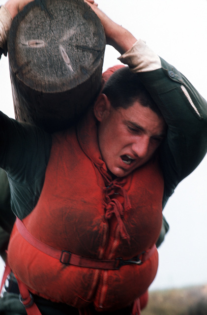 """A U.S. Navy Basic Underwater Demolition/Sea-Air-Land (SEAL) (BUD/S) trainees helps carry large logs during a """"hell week"""" exercise. Phase I of BUD/S training concludes with """"hell week,"""" when students' physical, emotional and mental abilities are tested under adverse conditions"""